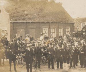 """Gemeentebestuur en inwoners van Lange Ruige Weide vóór het café """"De Lindeboom"""" bij gelegenheid van het 25-jarig regeringsjubileum van koningin Wilhelmina, 1923."""