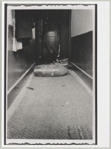 Een onontplofte bom, gevallen tijdens het bombardement van 13 mei 1940, ligt in de gang van een huis aan de Verlengde Hoogstraat in Montfoort (fotonummer M3598).